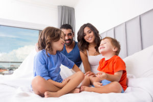 Children playing on parents bed wearing pajamas
